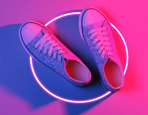 Scarpe da ginnastica alla moda. synth wave anni '80 e cerchio luminoso retrowave con un'estetica futuristica