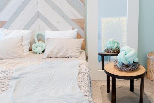 Spazioso appartamento alla moda con un design elegante in colori pastello verde, grigio e bianco con grandi finestre e pareti decorative. camera da letto e spazio cucina