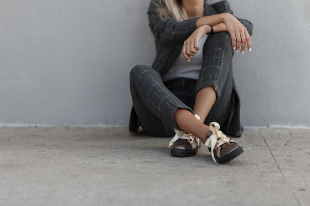 Ragazza alla moda alla moda in un abito grigio vintage con giacca, pantaloni e scarpe alla moda si siede vicino al muro grigio. signora di affari di moda. riposo