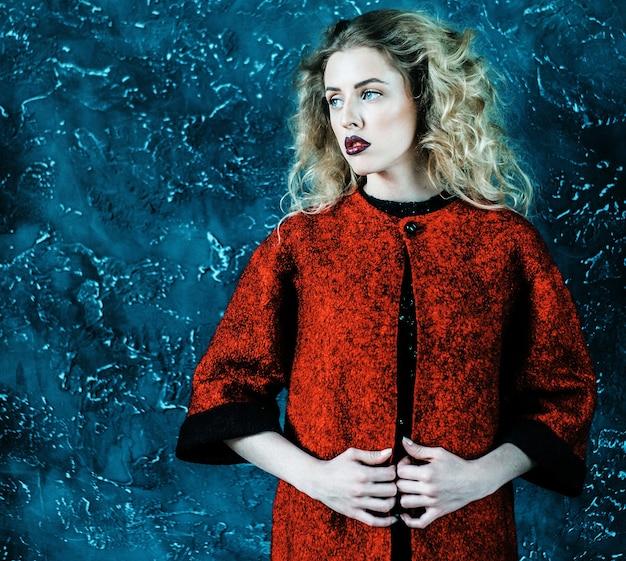 Donna alla moda alla moda vestita con un cappotto rosso