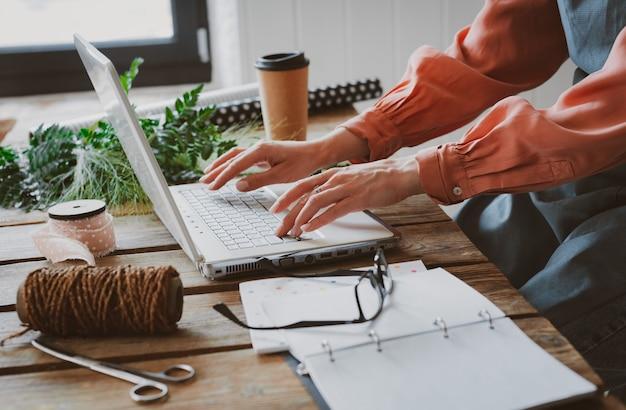 Donna alla moda alla moda con il grembiule che lavora ad un computer portatile