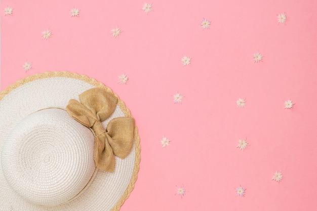 Cappello estivo alla moda con fiocco su sfondo rosa con fiori. vestiti e accessori alla moda per le donne. lay piatto.