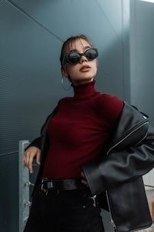Ragazza alla moda modello adolescente con occhiali da sole in una giacca di pelle nera con un maglione bordeaux si trova vicino a un muro di metallo scuro in città