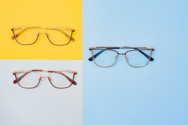 Occhiali alla moda alla moda per la correzione della vista su uno sfondo colorato, sfondo geometrico da carta di colori pastello