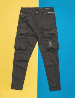 Pantaloni alla moda con grandi tasche su una superficie gialla e blu