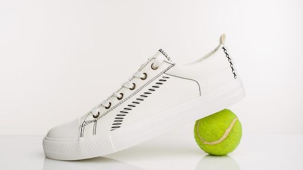 Scarpe da passeggio bianche alla moda con palla da tennis su sfondo bianco. - immagine