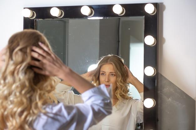 Cliente donna alla moda che guarda al suo riflesso nello specchio dopo l'acconciatura al salone di bellezza