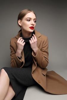 Donna alla moda in un cappotto. stile retrò, vestito nero,