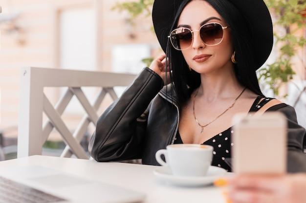 La donna alla moda in cappello elegante in occhiali da sole alla moda in abiti alla moda si siede e fa selfie su smartphone nella caffetteria. ragazza alla moda in gioventù nera indossa fotografie se stessa sulla terrazza estiva poen.
