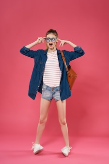 Fondo rosa di stile di estate dello zaino basato a figura intera della donna alla moda