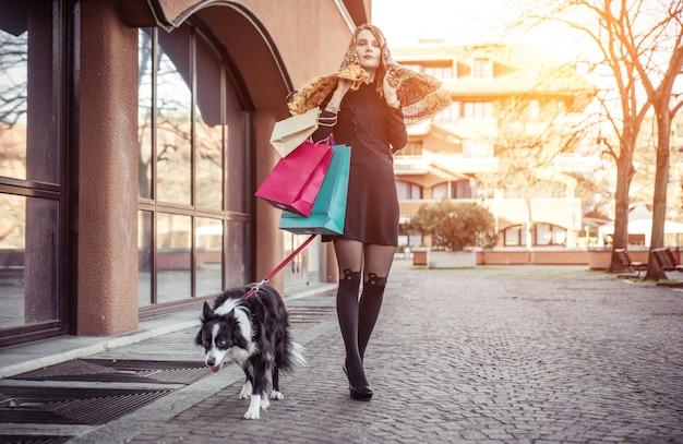 Donna alla moda e il suo cane border collie fare shopping nel centro della città