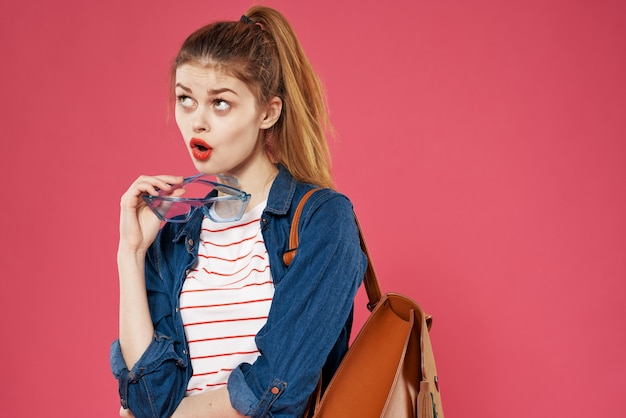 La donna alla moda che tiene lo zaino vestiti studente di apprendimento sfondo rosa foto di alta qualità