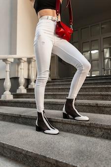 Donna alla moda in jeans in scarpe bianche e nere con una borsa rossa in posa sui gradini della città.