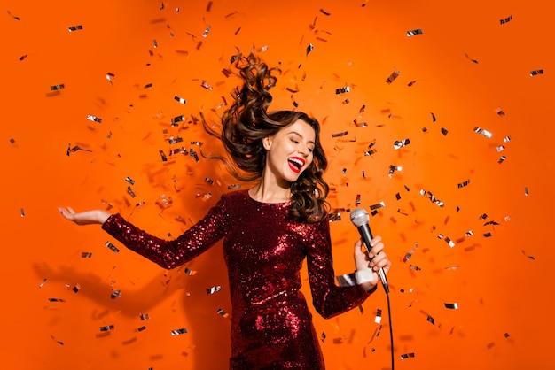 Donna alla moda in posa contro il muro arancione