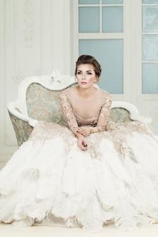 Donna alla moda seduta sulla poltrona