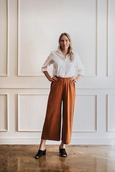 Donna alla moda in piedi vicino a un muro bianco
