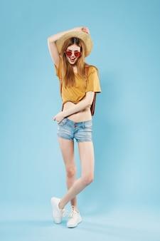 La donna alla moda in vestiti di estate sta a figura intera in posa sfondo blu
