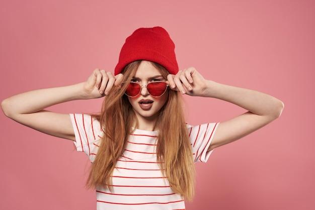 Moda donna occhiali da sole e cappello rosso studio sfondo rosa moda