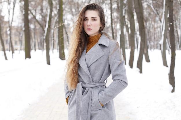 Donna alla moda che cammina in città in cappotto caldo