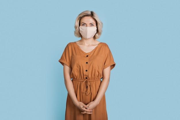 Donna alla moda che indossa un vestito e una mascherina medica che sorride alla macchina fotografica su una parete blu dello studio