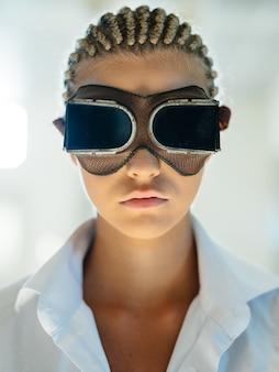 Donna alla moda con i dreadlocks sulla testa e in d occhiali di realtà virtuale su una luce