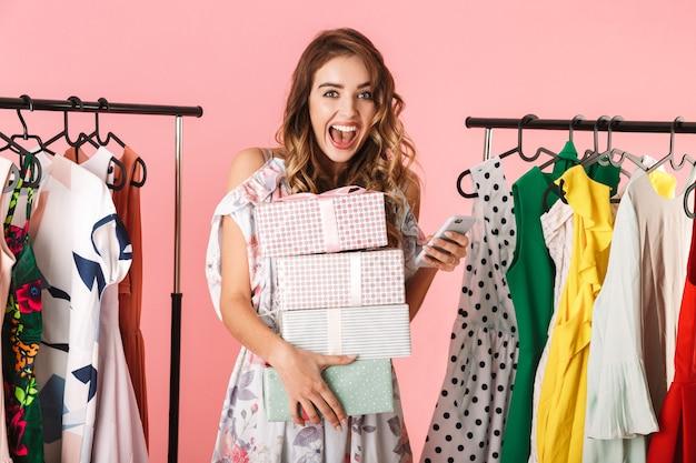 Donna alla moda con acquisto in piedi nel negozio vicino a stendibiancheria e utilizzando il telefono cellulare isolato in rosa