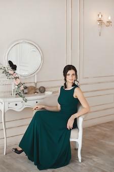 Donna alla moda con acconciatura alla moda in abito da sera e scarpe alla moda si siede alla toletta