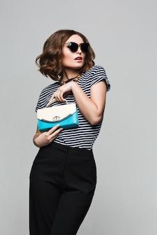 Donna alla moda con una borsa bianca e blu e grandi occhiali da sole rotondi. vestito in camicia a righe e pantaloni neri alla moda.