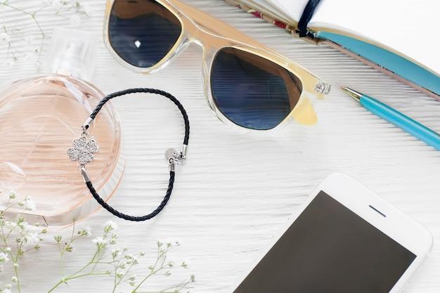Lavoro di donna alla moda con accessori femminili. smartphone con schermo vuoto con occhiali da sole, profumo, braccialetto, penna e taccuino sulla tavola di legno bianca