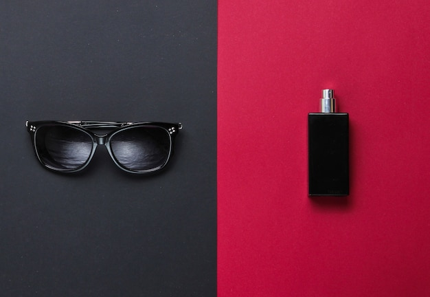 Accessori da donna alla moda. occhiali da sole, guanti in pelle nera, bottiglia di profumo su uno sfondo di carta. vista dall'alto, minimalismo