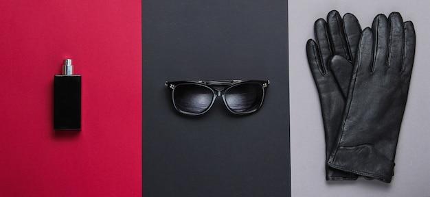 Accessori da donna alla moda. occhiali da sole, guanti di pelle nera, bottiglia di profumo. vista dall'alto, minimalismo