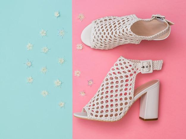 Scarpe estive bianche da donna alla moda con fiori sulla superficie turchese e rosa