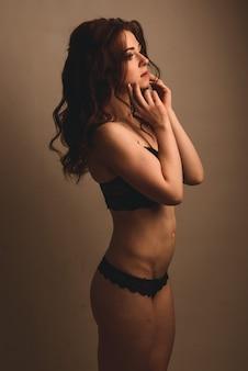 Giovane donna sensuale castana riccia alla moda in biancheria nera sexy