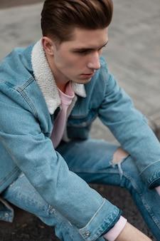 Moda giovane bell'uomo in vestiti alla moda blue jeans che riposano sulle mattonelle sulla strada. bel ragazzo con l'acconciatura alla moda in abito di jeans di moda giovanile si trova in città vicino alla strada. abbigliamento casual per uomo