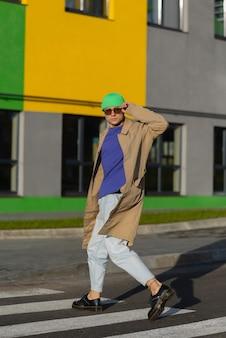 Alla moda giovane uomo bello in abiti eleganti attraversa le strisce pedonali della città