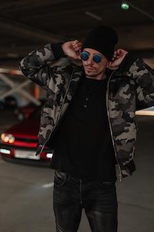 Modello alla moda giovane e bello in giacca invernale militare alla moda con occhiali da sole che indossano un cappello in città