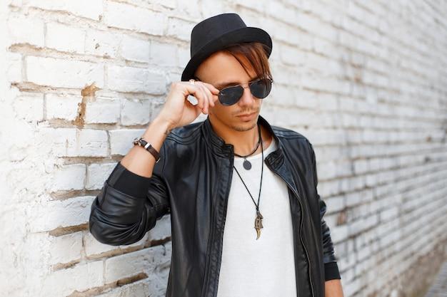 Alla moda giovane uomo bello che indossa occhiali da sole, un cappello nero e una giacca di moda elegante vicino al muro di mattoni bianchi vintage