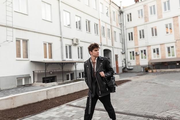 Uomo alla moda giovane hipster in un'elegante giacca di pelle nera con un'acconciatura alla moda in jeans con uno zaino vintage cammina per strada vicino agli edifici. modello di moda ragazzo europeo in città.