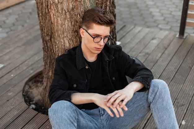 Giovane alla moda in occhiali alla moda in jeans vestiti alla moda che riposano vicino all'albero sulla terrazza estiva in città