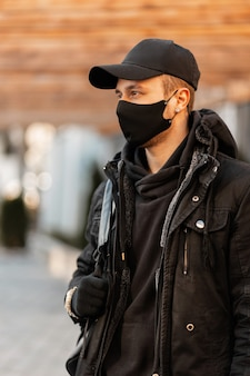 Modello alla moda del giovane con una maschera medica protettiva in vestiti alla moda, giacca invernale con una felpa con cappuccio e uno zaino cammina in città
