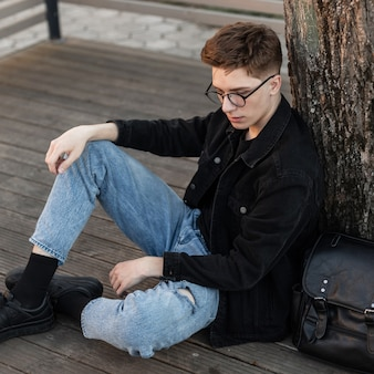 Giovane alla moda in occhiali vintage in abbigliamento casual in denim alla moda in scarpe da ginnastica con zaino in pelle