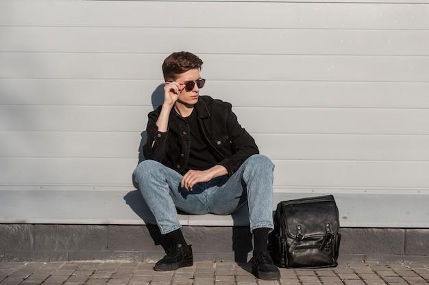 Giovane alla moda con occhiali da sole vintage in abiti casual eleganti in denim per giovani in scarpe da ginnastica
