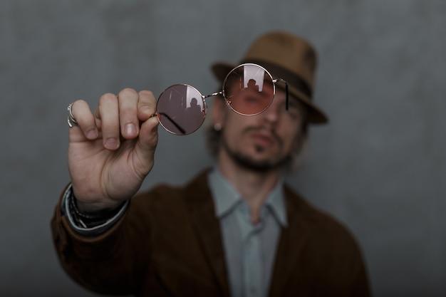 Il giovane alla moda con la barba in un cappello alla moda in abiti eleganti mostra alla fotocamera un paio di occhiali rosa rotondi vintage. modello di ragazzo brutale nella stanza. stile antiquato. concentrati sugli occhiali.