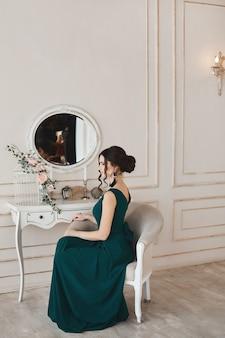 Giovane modella alla moda in abito da sera alla moda si siede in poltrona vicino alla toletta