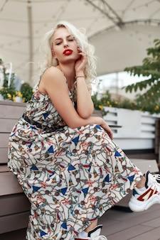 Donna alla moda giovane modella con labbra rosse in un vestito elegante con un motivo con scarpe seduto su una panca di legno in città