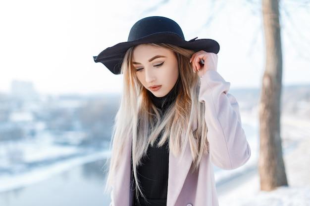 Giovane donna alla moda in un cappello vintage nero in stile retrò in un cappotto rosa alla moda in un abito lavorato a maglia è in piedi nella foresta in una calda giornata invernale