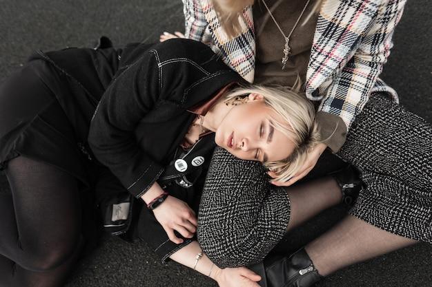 La giovane donna bionda alla moda in abiti eleganti neri dorme sull'asfalto con la sorella in giacca a scacchi