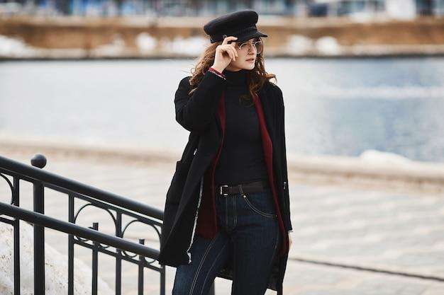 Giovane donna alla moda in un cappotto, un cappello alla moda e occhiali da sole in posa su uno sfondo urbano.