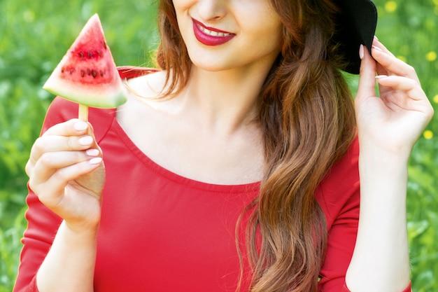 La giovane donna alla moda sta tenendo una fetta di anguria