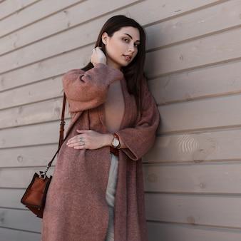 Il modello alla moda della giovane donna in cappotto alla moda con la borsa alla moda di cuoio posa vicino alla costruzione dai bordi. bella ragazza carina in abito primaverile alla moda sta riposando vicino alla parete di legno sulla strada. signora di bellezza.